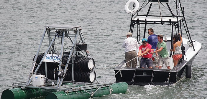 Staff photo by Cole Dittmer.  Humberto Covarrubias and Chris Matthews hold the SOROS desalinization apparatus in place while getting underway in Wrightsville Beach on Thursday, May 15.