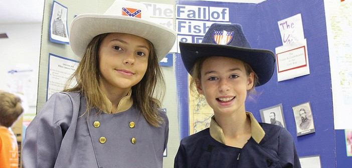 Staff photo by Cole Dittmer. Wrightsville Beach School fourth graders Avery Jones, left, and Riley Johnson present on the fall of Fort Fisher while dressed in Confederate and Union army uniforms at the WBS History and Service Learning Fair on Friday, May 9.