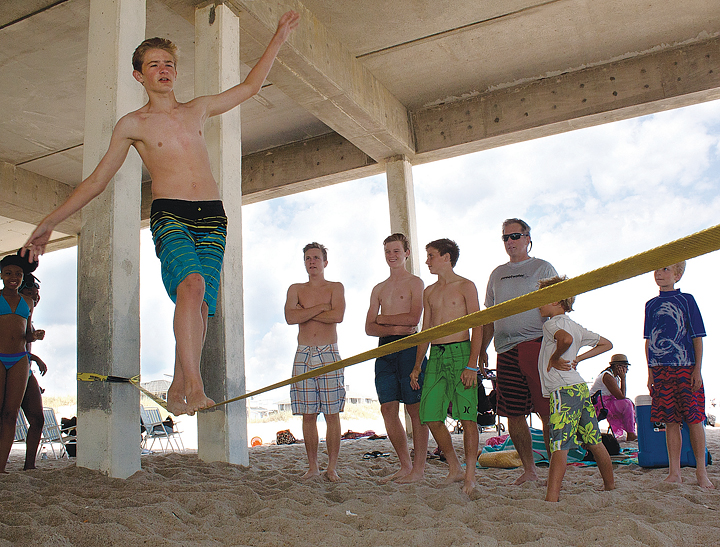 Staff photo by Emmy Errante. Austin Redenbaugh balances on a slackline tied between two pilings beneath Johnnie Mercer's Pier on Monday, May 26.