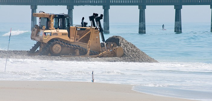 Staff photo by Allison Potter. A worker from Weeks Marine moves sand with a bulldozer on Wrightsville's beach strand Wednesday morning, May 14.