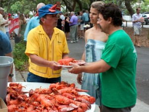 Don Hickey, from left, veteran lobster steamer offers a plate of the red hot crustacean to Allie and Dave DiBlasi during the 30th annual Harbor Island Lobster Fest and Block Party on Saturday, June 14.