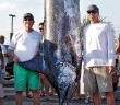 "Staff photo by Emmy Errante.  Bill Blount and ""Coverage"" captain Hunter Blount stand next to the 821-pound blue marlin that they caught during the Cape Fear Blue Marlin tournament in Wrightsville Beach on Saturday, May 31."