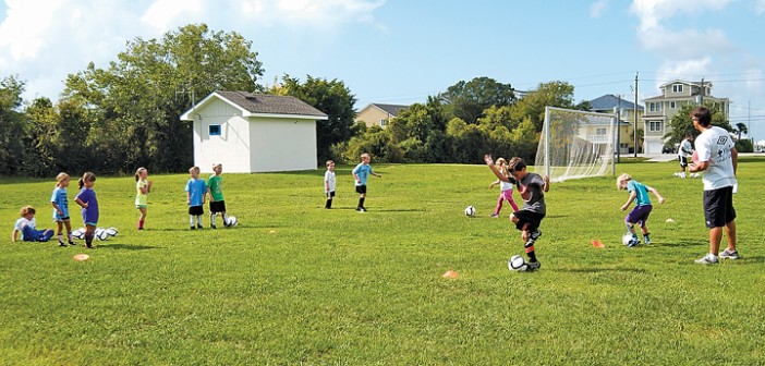 Lumina News file photo. Campers perform a dribbling drill with Hammerheads forward Andriy Budnyy, far right, during a soccer camp in Wrightsville Beach Park on Aug. 6, 2012.