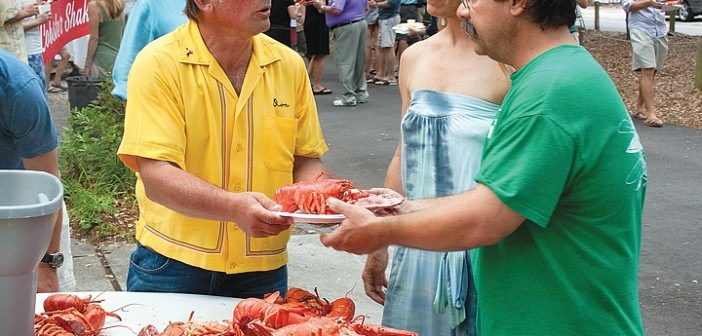 Staff photo by Emmy Errante. Volunteer Don Hickey serves freshly steamed lobsters to Allie and Dave DiBlasi at the Harbor Island block party held in conjunction with the 30th annual Lobsterfest to benefit Church of the Servant on June 14.