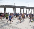 Staff photo by Emmy Errante. Competitors begin the beach run during the 2nd Annual Pier to Pier Run/Walk, Crab Crawl and SUP Race on Saturday, June 7 at Wrightsville Beach.