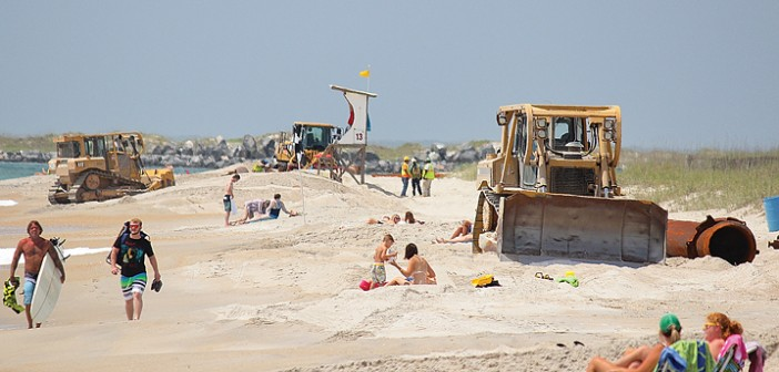 Staff photo by Cole Dittmer. Bulldozers from dredge contractor Weeks Marine work on removing the pipeline from the south end of Wrightsville Beach on Tuesday, June 3. With the Coastal Storm Damage Reduction project complete, the contractor has until June 13 to remove its equipment from the beach strand.