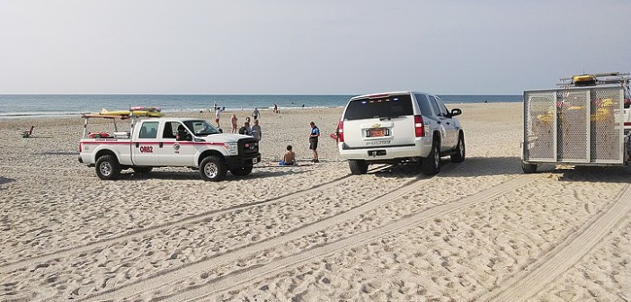 Staff photo by Pat Bradford, Wrightsville Beach Police and Ocean Rescue speak with a man suspected of underage consumption after the man was found unconscious, face down in the sand on Friday morning, June 20.