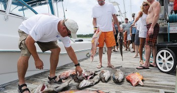 Lumina News file photo. Chuck Boyette, left, and Jeff Lanier bring the fish caught aboard Diversion to the Seapath Marina dock at the 2012 Wrightsville Beach Spearfishing Tournament.