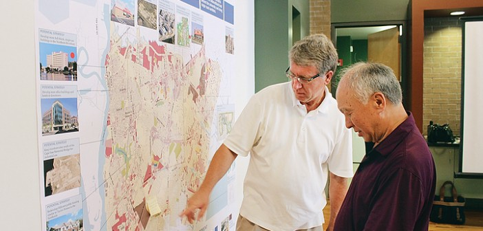 Staff photo by Cole Dittmer. Eddie Brock, left, and Richard Yang review one of the future visions maps during the city of Wilmington's public input session at Halyburton Park on Wednesday, June 25.