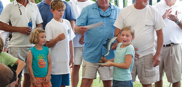Staff photo by Emmy Errante. The crew of the Decoy accept their first-place trophy at the Eddy Haneman Sailfish Tournament awards ceremony on Sunday, July 27 at Bridgetender Marina.