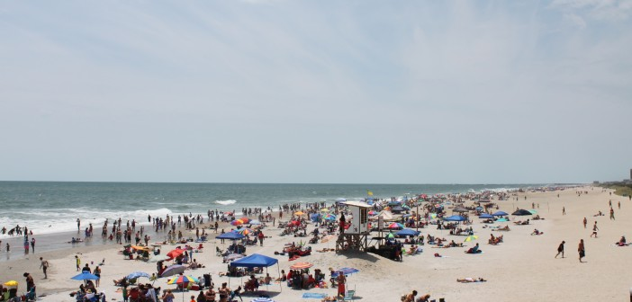 Staff photo by Miriah Hamrick.  Crowds dot the beach strand below Johnnie Mercer's Pier on Saturday, July 5.