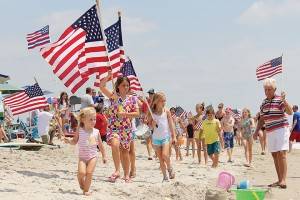Staff photo by Cole Dittmer. Children of all ages in the annual Hanover Seaside Club Fourth of July parade hold American flags high as they make a pass on the beach strand in front of the club.