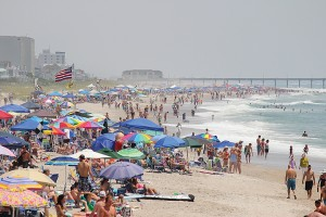 Staff photo by Cole Dittmer. Beachgoers pack the beach strand from Crystal Pier to Johnnie Mercer's Pier on the Fourth of July.