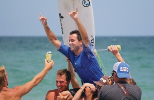 Staff photo by Cole Dittmer. Wrightsville Beach local Ben Bourgeois is greeted by a crowd of friends and family on the beach after winning the 9th annual O'Neill Sweetwater Pro-Am Sunday, July 13.