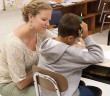 Staff photo by Allison Potter. Teacher Jessica Alphin helps a student at the Read to Achieve camp at Bradley Creek Elementary School Wednesday, July 16.