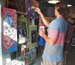 Staff photo by Emmy Errante. Guests admire the artwork of Mickey Stope at the Sticks, Stones and Broken Bones art show at Annex Surf Supply on Saturday, July 26.