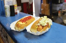 Staff photo by Cole Dittmer. The Trolly Stop's Surfer Dog with melted cheese, deli mustard and bacon bits, and the Carolina Dog with homemade chili, slaw and deli mustard are two of the hot dog stands most popular offerings.