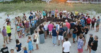 Staff photo by Emmy Errante. People gather at Wrightsville Beach Access 34 for a turtle nest excavation Tuesday, July 29 at 8:15 p.m.