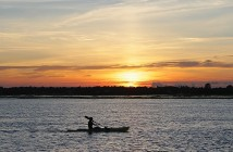 Staff photo by Cole Dittmer. A lone kayaker paddles north along Banks Channel right around sunset.