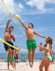 Staff photo by Emmy Errante. Mac Schott jumps above the net during a volleyball game near Crystal Pier at the University of North Carolina Wilmington's Beach Blast Tuesday, Aug. 19.