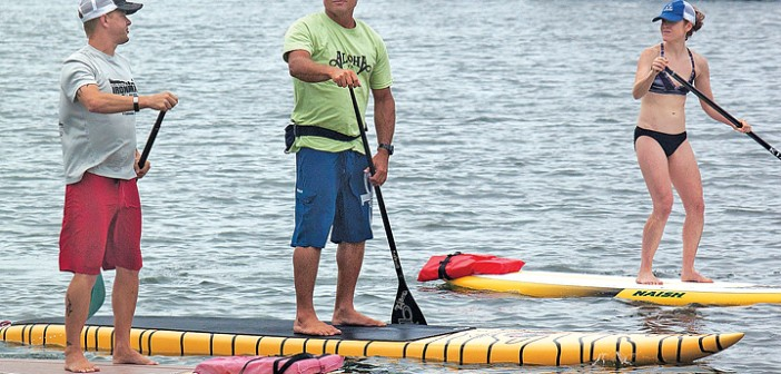 Staff photo by Emmy Errante. Legendary surfer and paddleboarder Dave Kalama, center, paddleboards in the Intracoastal Waterway with Scott and Leanne Johnson as a part of Pipeline to a Cure on Saturday, Aug. 2.