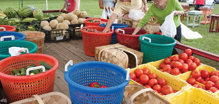 Staff photo by Emmy Errante. Customers fill their bags with produce from Edens Farms at the Wrightsville Beach Farmers' Market Monday, Aug. 25.
