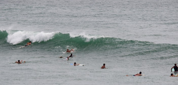 A crowd of surfers paddle for a wave on the north side of Crystal Pier on Tuesday, Aug. 5.