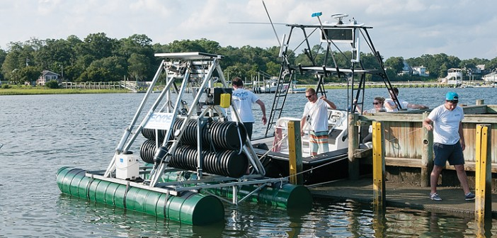 Staff photo by Allison Potter.  Recent graduates of the University of North Carolina Charlotte prepare to haul out their Swell Actuated Reverse Osmosis System at the public boat ramp in Wrightsville Beach Monday, Aug. 18.