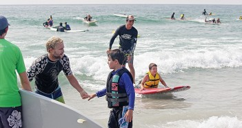 Staff photo by Cole Dittmer. Children experience a surf session at Wrightsville Beach with help from adult volunteers at the Surfers Healing autism surf day on Monday, Aug. 18.