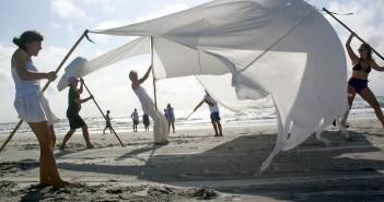 "Staff photo by Emmy Errante.  Karola Lüttringhaus and other artists and volunteers perform ""Volo,"" in which the SARUS Festival bird flies along the beach during the SARUS Festival for site-specific and experimental art performances at Wrightsville Beach Sunday, Aug. 24."