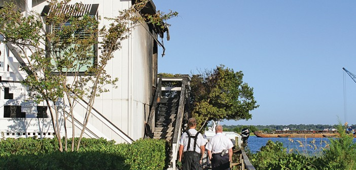 Staff photo by Cole Dittmer. Wrightsville Beach Fire Chief Frank Smith, left, walks with a fire marshal along the side of the house at 108 Water St. that caught fire in Wrightsville Beach around 3:30 a.m. Wednesday, Aug. 27.