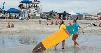 Lumina News file photo. Hannah Milligan and Nina Long share a high five after their longboard heat at the East Coast Wahine Championships Aug. 18, 2013 at Wrightsville Beach.