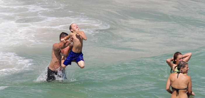 A father throws his son into the water north of Crystal Pier on Labor Day Monday, Sept. 1.