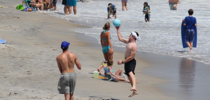 Friends play with a ball on the beach north of Crystal Pier on Labor Day Monday, Sept. 1.