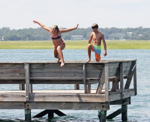 Staff photo by Cole Dittmer. Mary Suzanne Moore and Joe Stott jump off the Banks Channel dock of the Hanover Seaside Club around high tide on Labor Day Monday, Sept. 1.