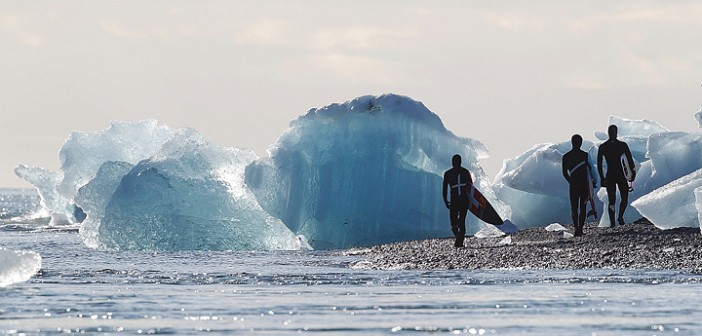 "Supplied photo by DJ Struntz. Surfers in the new Globe surf film ""Strange Rumblings in Shangri La,"" walk past small icebergs on the coast of Iceland."