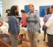 Staff photo by Cole Dittmer. California artist Russell Crotty, second from right, discusses his surf art with patrons during the opening of his exhibit at The Art Gallery in the University of North Carolina Wilmington's Cultural Arts Building Thursday, Sept. 4.