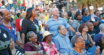 Staff photo by Emmy Errante.  Protestors hold hands at the Moral Monday rally Monday, Sept. 15 at RIverfront Park in downtown Wilmington.