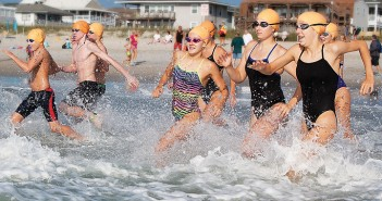 Lumina News file photo. Swimmers run into the water at the beginning of the Pier-2-Pier Swim Sept. 14, 2013 at Johnnie Mercer's Pier.