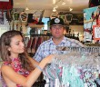 Staff photo by Cole Dittmer. South End Surf Shop owner Jeff DeGroote helps Melanie Torres look through the after summer sale swimwear Tuesday, Sept. 23. Sales and events are often used by beach businesses to keep customers coming after the summer tourist season.