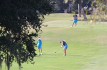 UNCW's Annette Lynch hits a shot on No. 18 while UNCW coaches look on.