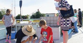 Staff photo by Cole Dittmer. Margaret Robison, Cape Fear Community College Vice President of Institutional Advancement, observes Wrightsville Beach School marine science instructor Cissy Brooks and third grader Eathan Quinn studying a blue crab pulled from the waters around the school's sound side dock Thursday, Oct. 9, as part of the Walk In My Shoes program.