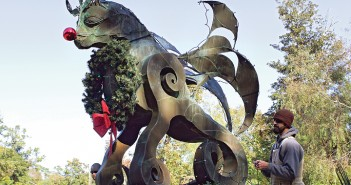 Staff photo by Cole Dittmer. Gregg Sales decorates the Minnie Evans influenced sculpture near the front gate of Airlie Gardens for Enchanted Airlie Thursday, Nov. 20.