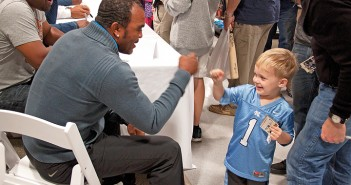 Staff photo by Emmy Errante. Three-year-old Sam Horton gets a fist bump from retired Major League Baseball player Tony Womack during the Willie Stargell Celebrity Golf autograph signing at Dick's Sporting Goods in Mayfaire Town Center Saturday, Nov. 8.
