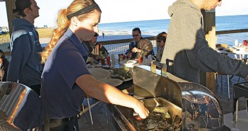 Staff photo by Cole Dittmer. A server from the Oceanic Restaurant dishes out some Stump Sound oysters for the buffet during the Wrightsville Beach Chamber of Commerce oyster roast Sunday, Nov. 2.