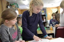 Staff photo by Cole Dittmer. Dolphin Tales writers Bella Ellison and Olivia d'Ancie review an article at Wrightsville Beach School Friday, Dec. 12.