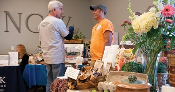 Lumina News file photo. Tony Bishop of the Wilmington Riverfront Farmers' Market, left, speaks with AJ Labret by the Poplar Grove Plantation Farmers' Market table during Feast Down East March 1, 2013 at the University of North Carolina Wilmington's Burney Center.