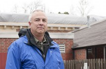 Staff photo by Allison Potter. Dick Jones, President and CEO of the Wilmington Family YMCA, stands at the back of the YMCA building where a tarp covers roof damage.