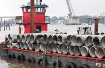 Staff photo by Allison Potter. A barge at Atlantic Coast Industrial, on the Cape Fear River, is loaded with pipes that will be dropped onto artificial reefs off Wrightsville's coast.