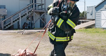Staff photo by Allison Potter. In full turnout gear, Stuart Farrow drags a 150-pound dummy 100 feet as part of the Wrightsville Beach Fire Department annual fitness assessment Saturday, March 21.